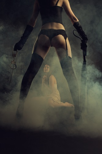 Beautiful cute model in white dress stands on knees next to legs of her dominatrix with lash and handcuffs in smoke